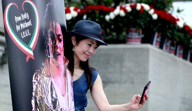 Eriko Ono, 49, of Tokyo takes a selfie with a poster as hundreds of Michael Jackson fans gathered at Forest Lawn Cemetery in Glendale to pay tribute on the 10th anniversary of the death of the King of Pop on June 25, 2019. (Raul Roa / Staff Photographer)