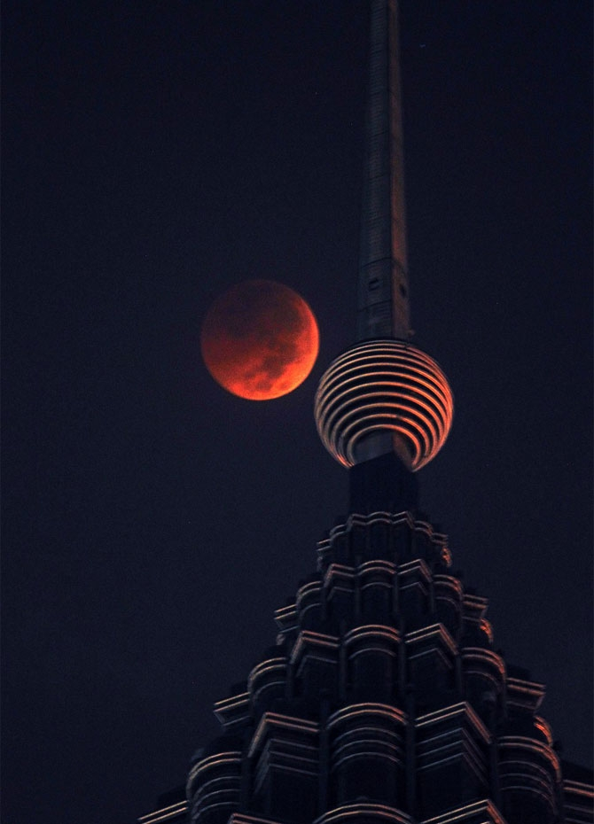 A full Blood Moon sets over Petronas Twin Tower during the complete lunar eclipse in Kuala Lumpur, Malaysia