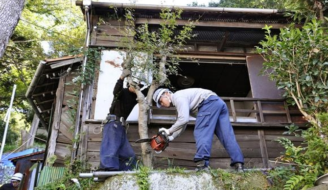 Workers prepare to dismantle an abandoned home. Many families forget to register the new owner when properties are passed down. © Kyodo