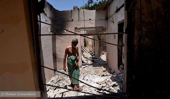Mohamed Najimudeen inspects damage to his home from the violence